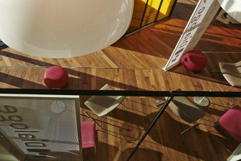 Vue depuis la mezzanine. Parquet noyer, luminaires, mobilier coloré...